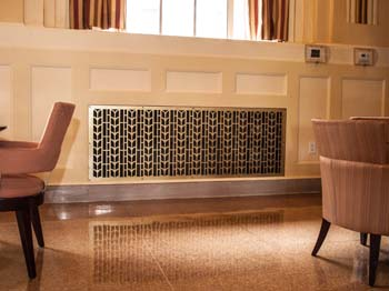 image of decorative metal grille on living room radiator | Coco Architectural
